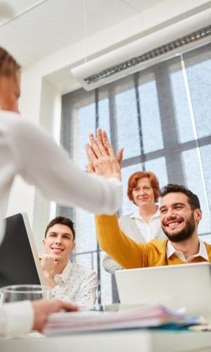 Kollegen im Business Team feiern mit High Five einen Erfolg im Computer Workshop